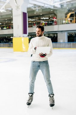 Cheerful man standing on skating rink with laptop stock vector