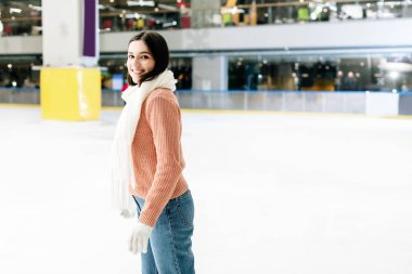 Beautiful happy girl in sweater and scarf skating on rink stock vector
