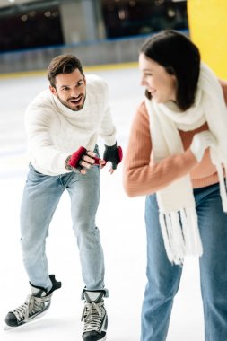 Excited young couple having fun while skating on rink stock vector