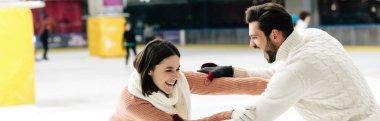 Panoramic shot of cheerful young couple having fun on skating rink stock vector