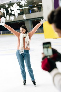 Selective focus of man taking photo of excited woman on smartphone on skating rink stock vector