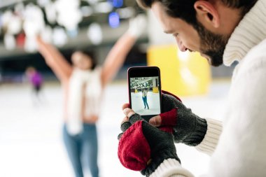 Selective focus of smiling man taking photo of woman on smartphone on skating rink stock vector