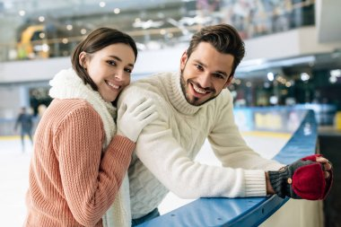 Young positive couple in sweaters spending time on skating rink stock vector