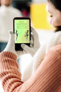 KYIV, UKRAINE - NOVEMBER 15, 2019: cropped view of woman in gloves holding smartphone with best shopping app on screen stock vector