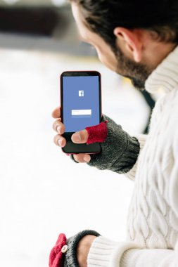 KYIV, UKRAINE - NOVEMBER 15, 2019: cropped view of man in gloves holding smartphone with facebook app on screen, on skating rink stock vector