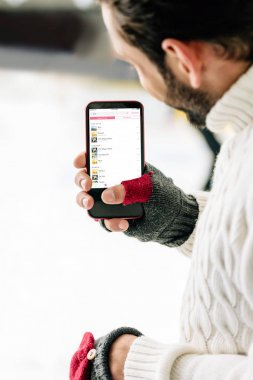 KYIV, UKRAINE - NOVEMBER 15, 2019: cropped view of man in gloves holding smartphone with apple music app on screen, on skating rink stock vector