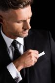 Jóképű üzletember szabályozza zsebkendő elszigetelt fekete
