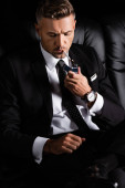 Fotografie schöner Geschäftsmann zündet Zigarette mit Feuerzeug auf Couch isoliert auf schwarz an