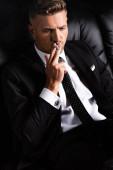Elgondolkodó üzletember cigizik a kanapén elszigetelve a fekete