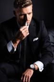 Kijev, Ukrajna - október 11, 2019: Pensive businessman smoking iqos isolated on black