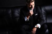 Kijev, Ukrajna - október 11, 2019: Üzletember dohányzik iqos miközben ül a kanapén elszigetelt ob fekete