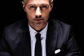 Egy jóképű üzletember portréja, amint a fekete kamerát nézi.