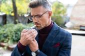 Jóképű üzletember szemüvegben cigarettát gyújtott a városi utcában.