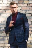 Fotografie schöner Geschäftsmann raucht Zigarette und schaut in die Kamera mit Backsteinmauer im Hintergrund