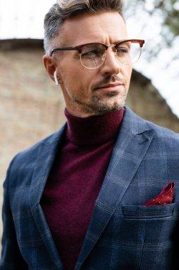 Handsome businessman in wireless earphones looking away outdoors stock vector