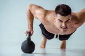 Photo sexy muscular bodybuilder with bare torso doing push ups with kettlebell on grey