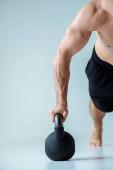 částečný pohled na sexy svalové kulturista s holým trupem dělat kliky s kettlebell izolované na šedé