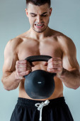 Photo tense sexy muscular bodybuilder with bare torso exercising with kettlebell isolated on grey