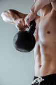 Photo cropped view of sexy muscular bodybuilder with bare torso exercising with kettlebell isolated on grey