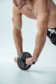 Ausgeschnittene Ansicht eines sexy muskulösen Bodybuilders mit nacktem Oberkörper, der mit Bauchtrainer auf grauem Hintergrund trainiert