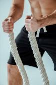 Ausgeschnittene Ansicht eines sexy muskulösen Bodybuilders mit nacktem Oberkörper, der mit einem Kampfseil isoliert auf grau trainiert