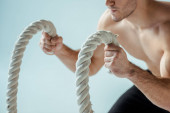 cropped view of sexy muscular bodybuilder with bare torso exercising with battle rope isolated on grey