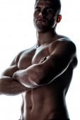 sexy svalnatý kulturista s holým trupem pózující se zkříženými pažemi ve stínu izolované na bílém