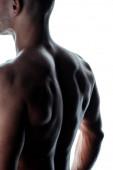 sexy kulturista se svalnatými zády ve stínu izolované na bílém