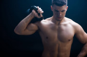 Photo sexy muscular bodybuilder with bare torso excising with kettlebell on black background