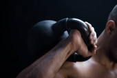 Photo cropped view of muscular bodybuilder excising with kettlebell isolated on black