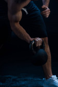 Photo cropped view of sexy muscular bodybuilder excising with kettlebell on black background