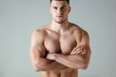 sexy muskulöser Bodybuilder mit nacktem Oberkörper posiert mit verschränkten Armen isoliert auf grau