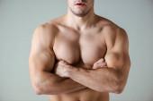 Ausgeschnittene Ansicht von sexy muskulösen Bodybuilder mit nacktem Oberkörper posiert mit verschränkten Armen isoliert auf grau