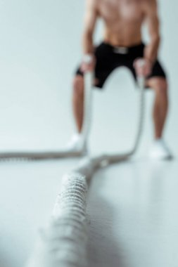 selective focus of sexy muscular bodybuilder with bare torso exercising with battle rope on grey background