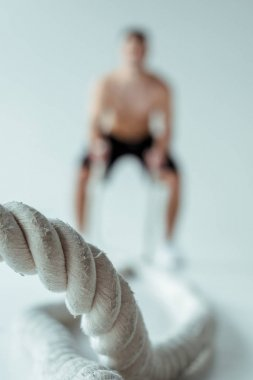 selective focus of man exercising with battle rope on grey background