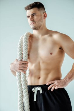 low angle view of sexy muscular bodybuilder with bare torso posing with battle rope isolated on grey