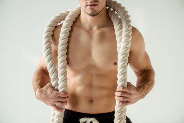 partial view of sexy muscular bodybuilder with bare torso posing with battle rope isolated on grey