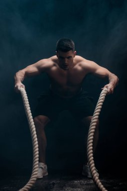 sexy muscular bodybuilder with bare torso excising with battle rope on black background with smoke
