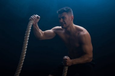 tense muscular bodybuilder with bare torso excising with battle rope on black background with smoke