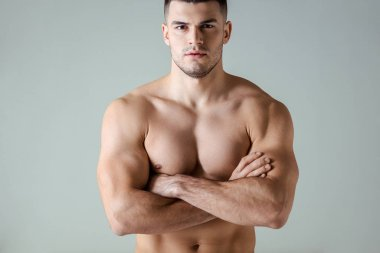Sexy muscular bodybuilder with bare torso posing with crossed arms isolated on grey stock vector