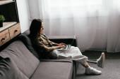 Oldalnézet a nő lábprotézis segítségével laptop kanapén a nappaliban