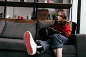 Szelektív fókusz fiatal nő műláb simogató mopsz kutya kanapén a nappaliban