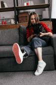 Szelektív fókusz vonzó nő láb protézis simogató mopsz kutya kanapén