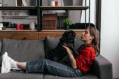 Boční pohled mladé ženy s protézou nohy hrát s pug na gauči v obývacím pokoji