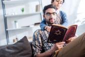 selective focus of jewish father and son reading tanakh in apartment