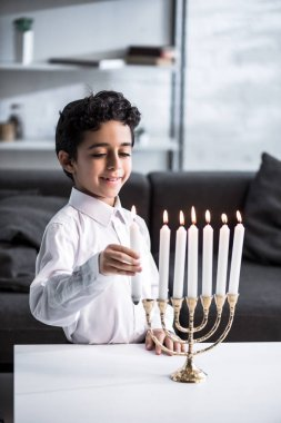 Cute and smiling jewish boy in shirt holding candle stock vector