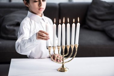 Cropped view of cute jewish boy in shirt holding candle stock vector