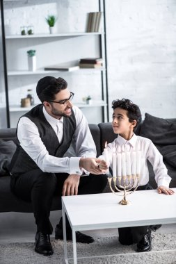 Smiling jewish father and son holding candle in apartment stock vector