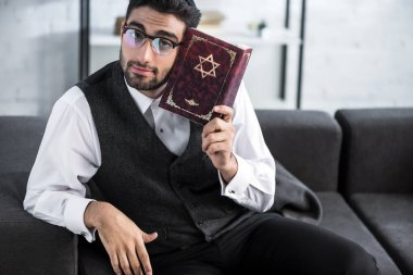Handsome jewish man in glasses holding tanakh and looking at camera stock vector
