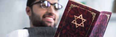 Panoramic shot of smiling jewish man in glasses reading tanakh stock vector
